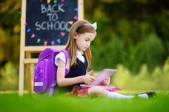 Adorable little girl using computer tablet while sitting on a grass on summer day Royalty Free Stock Photography