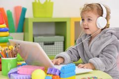 Little girl using laptop and headphones Stock Photos