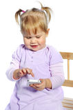 Adorable little girl using mobile phone on white background Royalty Free Stock Photo