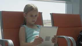 Adorable little girl using tablet at airport while waiting for their flight. Traveling abroad with kids. Adorable little girl using tablet at airport while stock video