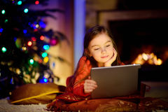 Adorable little girl using a tablet pc by a fireplace on Christmas evening Stock Images