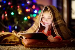 Adorable little girl using a tablet pc by a fireplace on Christmas evening. Adorable little girl using a tablet pc by a fireplace on warm Christmas evening Royalty Free Stock Images