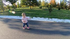 Adorable little girl walk in the park in october. Cute ten month baby walk. Beautiful happy girl. Autumn mood