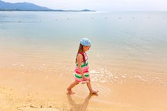Adorable little girl walking along white sand Caribbean beach. royalty free stock images