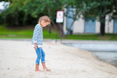 Adorable little girl walking along white sand near the lake. Adorable little girl walking in the city by the lake royalty free stock photos