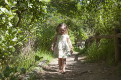 Adorable little girl walking down path. Adorable little girl walking down bushy path Royalty Free Stock Photography