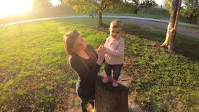 Adorable little girl walking in the park with mom in october. Cute ten month baby walk. Beautiful happy girl. Autumn