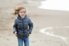 Adorable little girl walking by the seashore Stock Photo