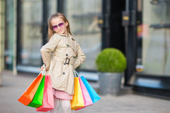 Adorable little girl walking with shopping bags outdoors in Europe. Fashion toddler kid in european city outdoors Royalty Free Stock Photo