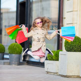 Adorable little girl walking with shopping bags outdoors in Europe. Fashion toddler kid in european city outdoors Royalty Free Stock Image