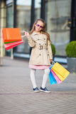 Adorable little girl walking with shopping bags outdoors in Europe. Fashion toddler kid in european city outdoors Royalty Free Stock Photography