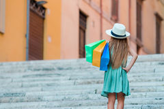 Adorable little girl walking with shopping bags outdoors in Rome. Fashion toddler kid in Italian city with her shopping Royalty Free Stock Image