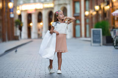 Adorable little girl walking with shopping bags in Paris outdoors Stock Photography