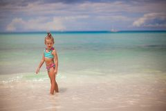 Adorable little girl walking in the water on Stock Photography
