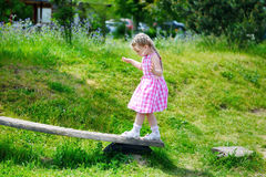 Adorable little girl walking on wood on sunny summer day. Adorable little girl walking on wood on summer day Royalty Free Stock Photo