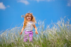 Little girl walks on the field Stock Photography