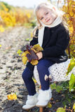 Adorable little girl in warm clothes, autumn time. Adorable happy little girl with is wearing winter clothes and sitting on the chair with autumn leaves on the Royalty Free Stock Photography