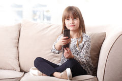 Adorable little girl watching tv. Portrait of adorable little girl sitting at living and holding in her hands a remote control while watching tv Stock Photos