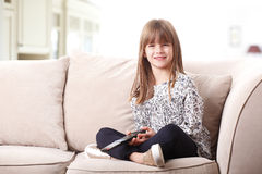 Adorable little girl watching tv. Portrait of adorable little girl sitting at living and holding in her hands a remote control while watching tv Stock Images