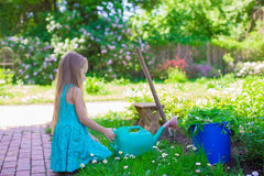 Adorable little girl with a watering can at big Royalty Free Stock Photos