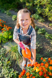 Adorable little girl watering flowers Stock Photos