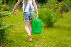 Adorable little girl watering flowers and plants Royalty Free Stock Photos
