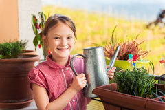 Adorable little girl watering plants on the balcony Royalty Free Stock Images