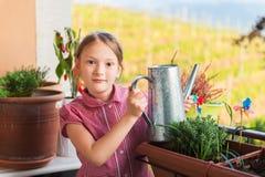 Adorable little girl watering plants on the balcony Stock Image