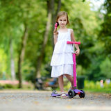 Adorable little girl wearing beautiful dress riding her scooter Royalty Free Stock Image
