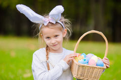 Adorable little girl wearing bunny ears with a basket full of Easter eggs on spring day outdoors Royalty Free Stock Photography