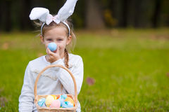 Adorable little girl wearing bunny ears playing with Easter eggs on spring day outdoors Stock Image