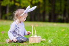 Adorable little girl wearing bunny ears playing with Easter eggs on spring day outdoors Stock Images