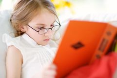 Adorable little girl wearing eyeglasses reading a book in white living room Royalty Free Stock Image