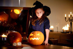 Adorable little girl wearing Halloween costume having fun with carved pumpkin Stock Images