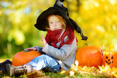 Adorable little girl wearing halloween costume having fun on a pumpkin patch on autumn day Stock Image