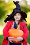 Adorable little girl wearing halloween costume having fun on a pumpkin patch Stock Photo