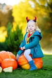 Adorable little girl wearing halloween costume having fun on a pumpkin patch Royalty Free Stock Photography