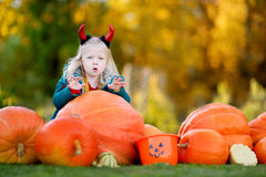 Adorable little girl wearing halloween costume having fun on a pumpkin patch Stock Photo
