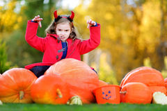 Adorable little girl wearing halloween costume having fun on a pumpkin patch Royalty Free Stock Image