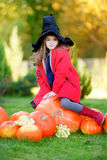Adorable little girl wearing halloween costume having fun on a pumpkin patch Royalty Free Stock Images
