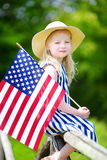 Adorable little girl wearing hat holding american flag outdoors on beautiful summer day Stock Image