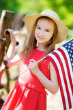 Adorable little girl wearing hat holding american flag outdoors on beautiful summer day Stock Photos