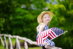 Adorable little girl wearing hat holding american flag outdoors on beautiful summer day Stock Images