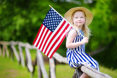 Adorable little girl wearing hat holding american flag outdoors on beautiful summer day Royalty Free Stock Images