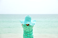 Adorable little girl wearing hat standing at beach during summer vacation. Royalty Free Stock Photography