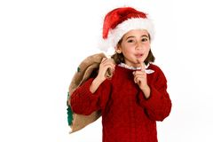 Adorable little girl wearing santa hat carrying gift bag Royalty Free Stock Image
