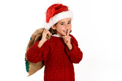 Adorable little girl wearing santa hat carrying gift bag. Isolated on white background. Winter clothes for Christmas Royalty Free Stock Photography