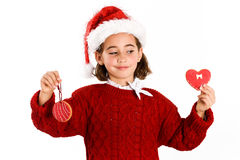 Adorable little girl wearing santa hat with Christmas cookies Stock Image