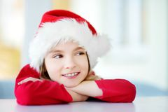 Adorable little girl wearing Santa hat on Christmas morning Stock Photo
