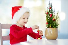 Adorable little girl wearing Santa hat decorating small Christmas tree in a pot on Christmas morning Stock Image